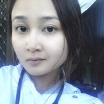 A girl is looking directly at the camera. She is wearing a white shirt and has dark brown hair.