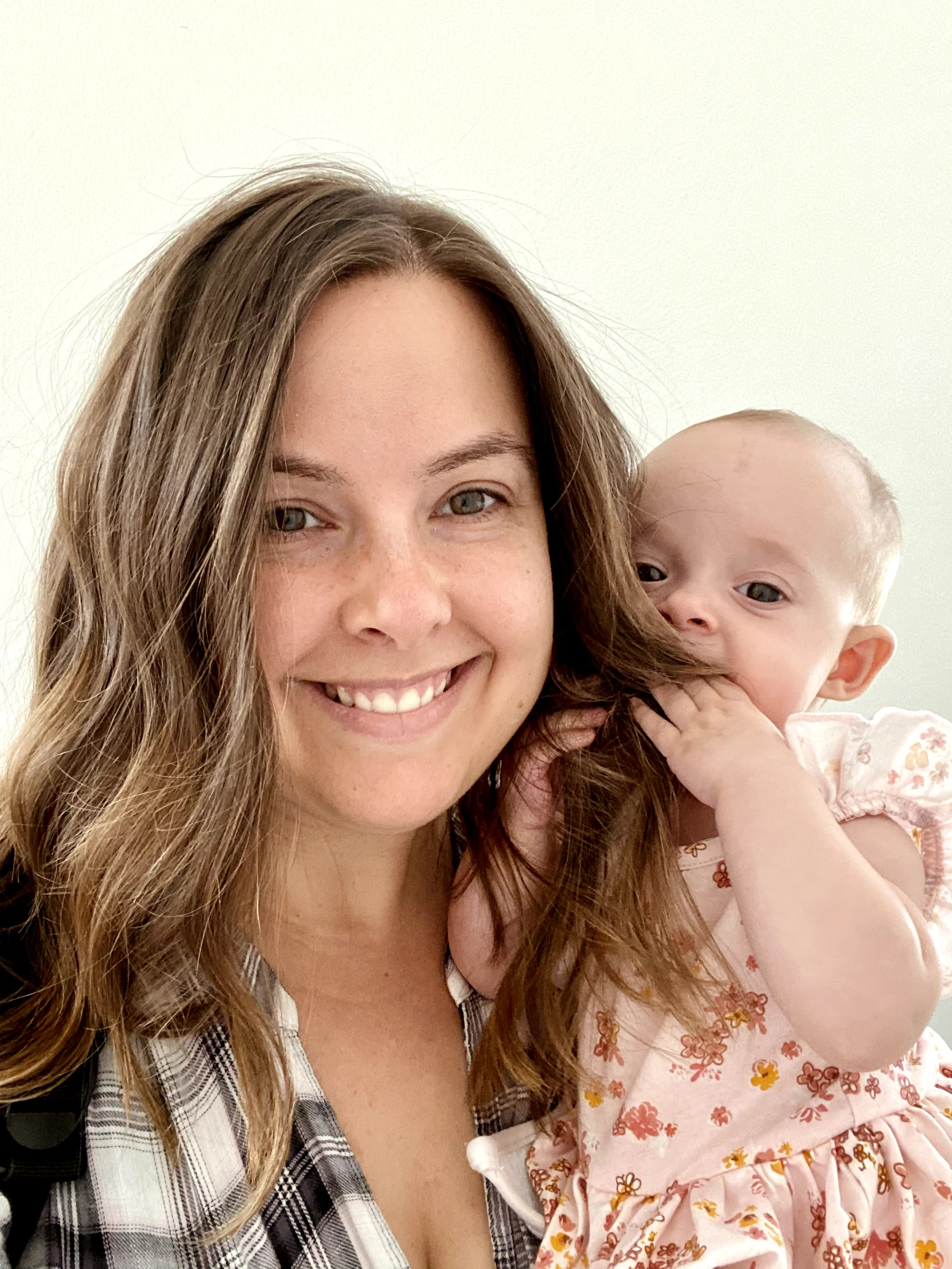 A smiling woman is holding a baby.